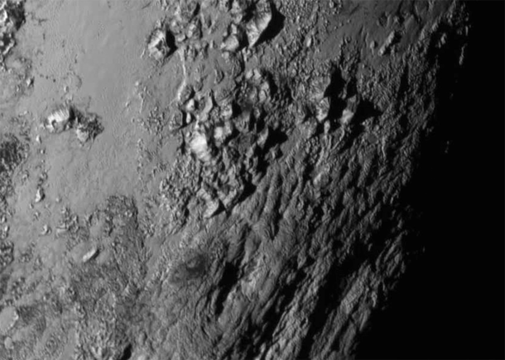 """This close-up image of the surface of Pluto is as remarkable for what it shows as for what it does not show. Returned from NASA's New Horizon's spacecraft last week, the image shows a small region about 150 miles wide and long near Tombaugh Regio, the newly named """"Heart of Pluto."""" The smooth surface, jagged icy peaks and total absence of impact craters indicate a very young surface, geologically speaking, a discovery that took mission scientists pleasantly by surprise."""