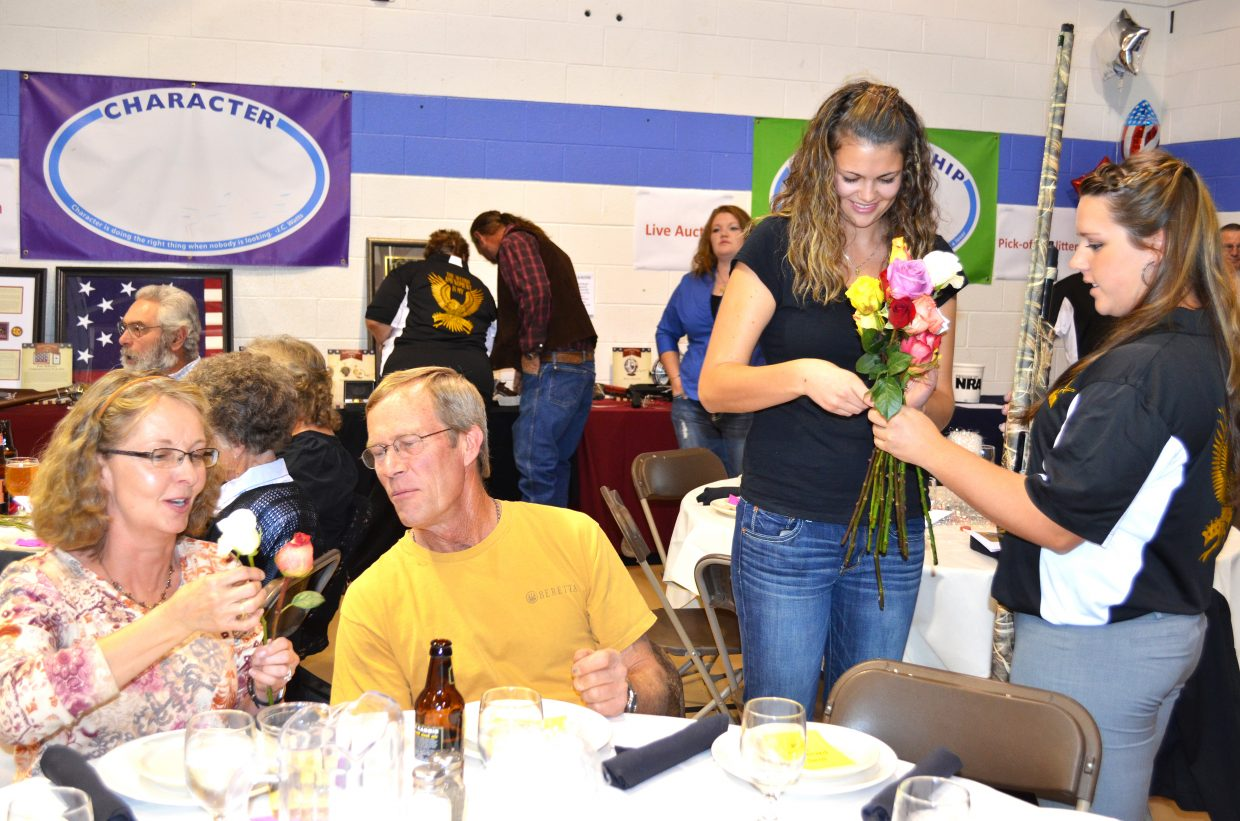 Larona and Dwight McPherson, seated, buy roses and tickets from Yampa Valley Friends of NRA members Hannah Beckett, left and Miranda Blomquist to enter a drawing for the camouflage rifle Blomquist is holding.