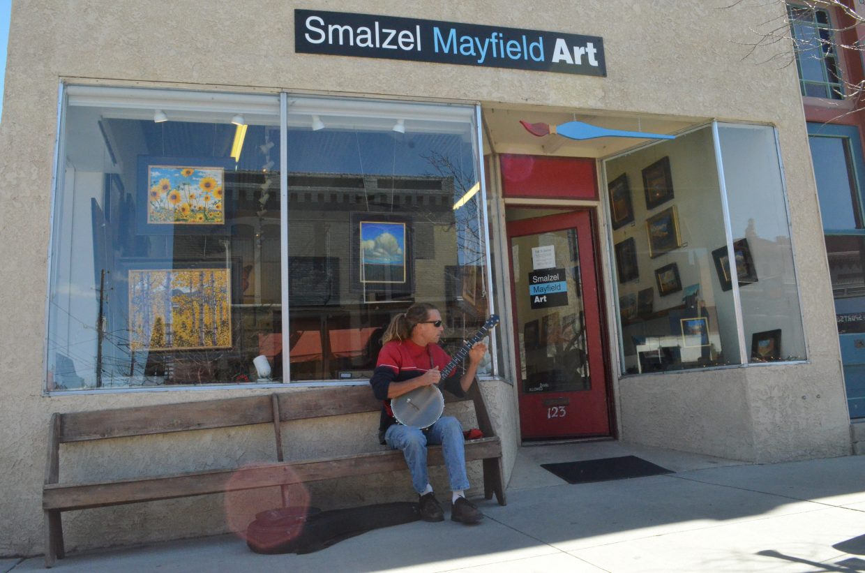 Stephen Smalzel strums a few tunes on his banjo in front of his gallery. He has lived in Salida for more than 20 years as an artist and musician.