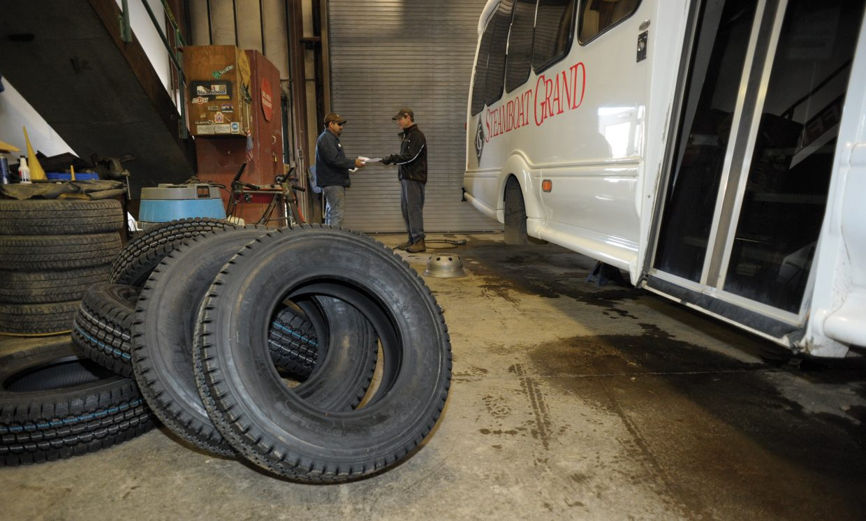 Sean Luciano takes a break from changing the tires on a Steamboat Grand shuttle van to accept a delivery at Steamboat Ski Area's maintenance shop.