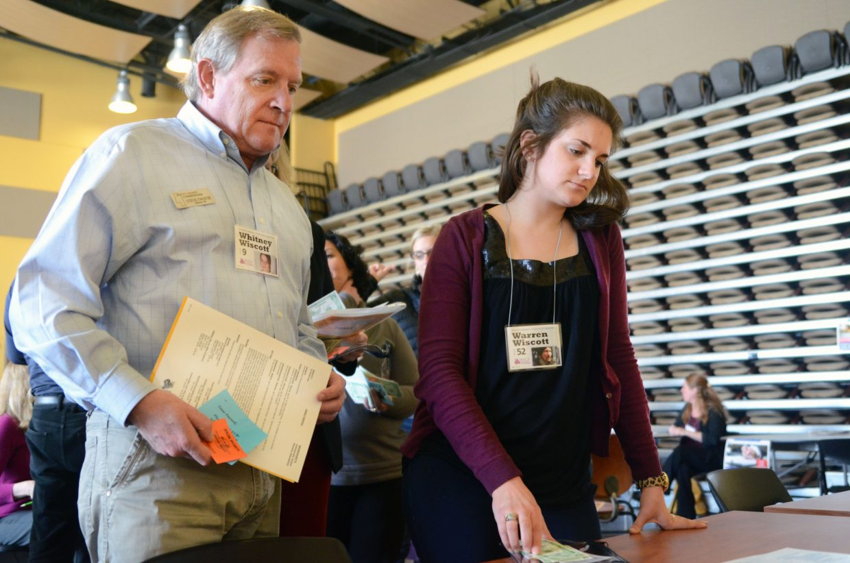 "Routt County Commissioner Steve Ivancie, left, and Becky Kruger, of Partners in Routt County, wait in line at the cash advance table during the March 6 poverty simulation at Colorado Mountain College's Allbright Auditorium. Ivancie and Kruger were part of the ""Wiscott family."""