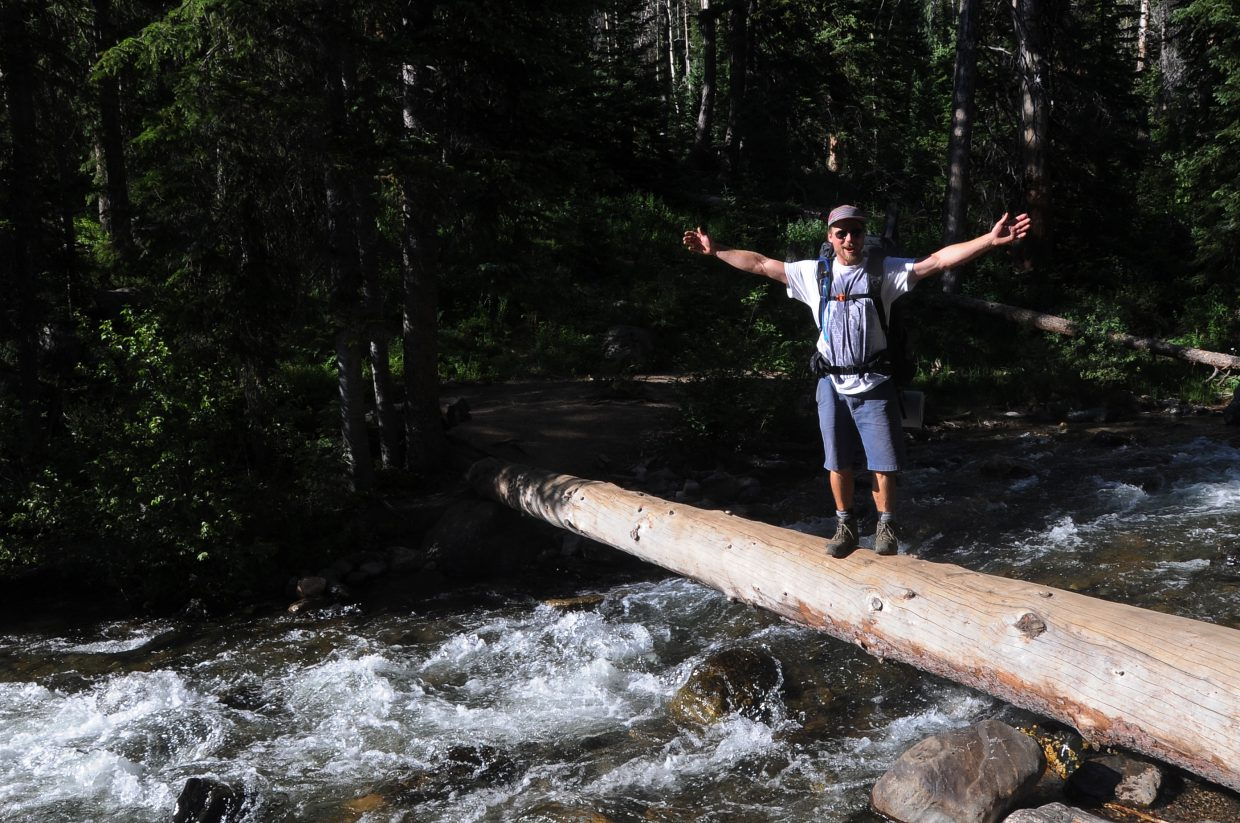 Alec Sobotka takes a moment to celebrate at the halfway point of his log crossing at Gold Creek in the Zirkel Wilderness. Backpackers must have good balance to make the trek across creeks in the early spring.