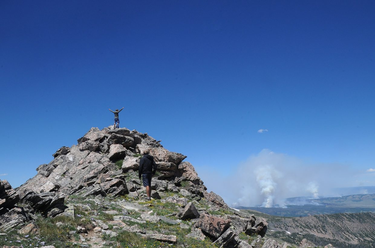 Alec Sobotka celebrates after reaching the summit of Mount Zirkel as the raging Beaver Creek Fire puts up smoke in the distance.