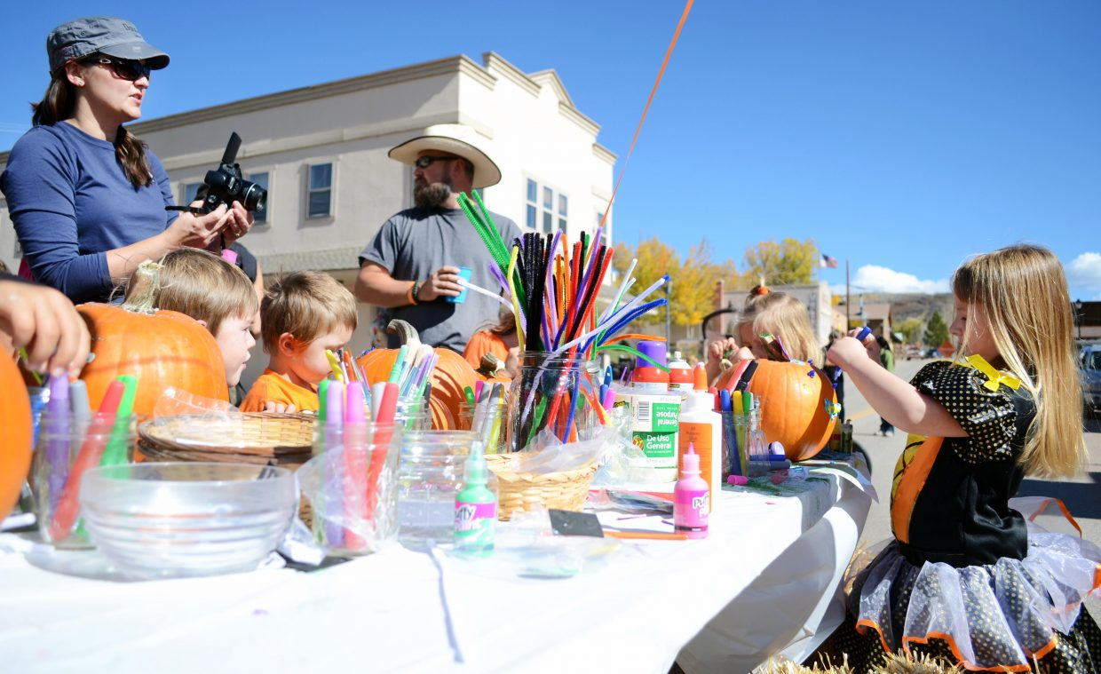Children gather around a picnic table to paint and decorate pumpkins Sunday during Oak Creek's 2014 Oaktoberfest, held along the town's Main Street.