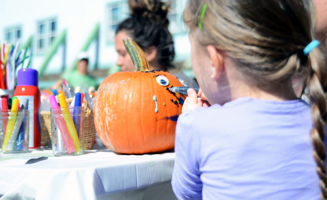 Seva Jonathans, 3, paints her pumpkin with some puff paint Sunday during Oak Creek's 2014 Oaktoberfest.