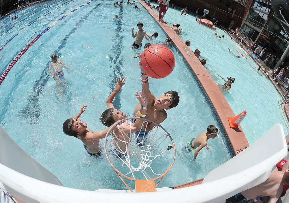 July 2012 — When the temperatures get hot in the summer, the waters of the Old Town Hot Springs are a great place to find photographs for the newspaper. On this day, Steamboat Springs resident Evan Barbier looked to dunk the ball during a pick-up basketball game. A fisheye lens and great light helped land this shot on the front page.
