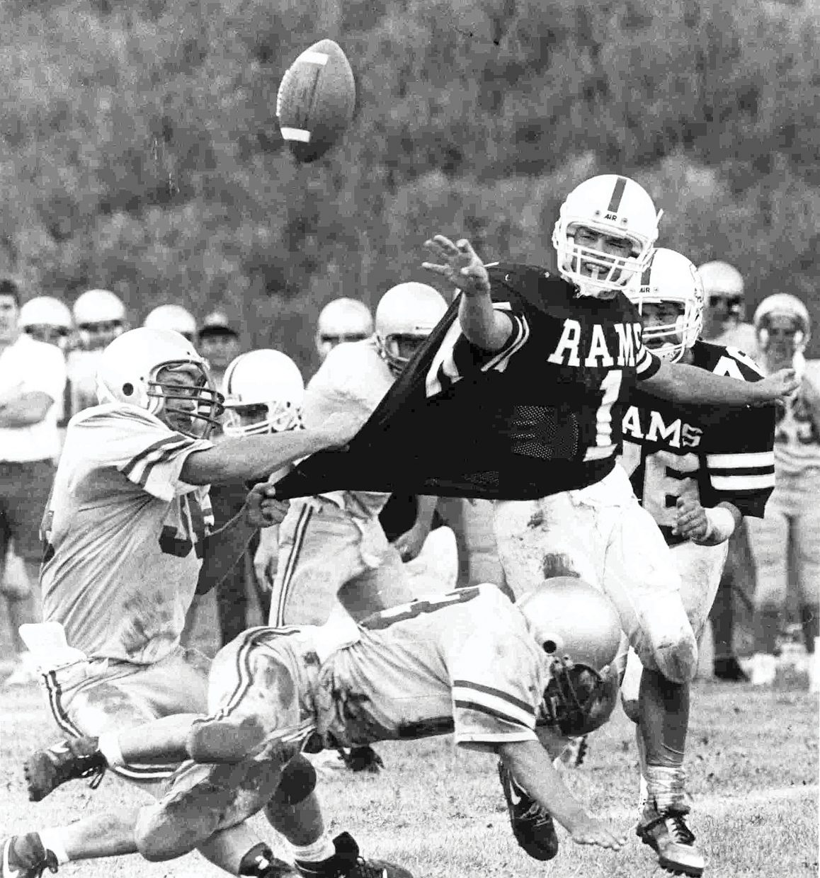 Unknown — I can't remember the exact year this photograph was taken, but the cool thing is it sums up just about every Soroco High School football game I've ever covered. The tough-as-nails quarterback making the pitch despite the fact that he's being pulled down from behind and tackled at the same time shows the traditional character of Rams' football teams. The mud on the jersey was just an added bonus.