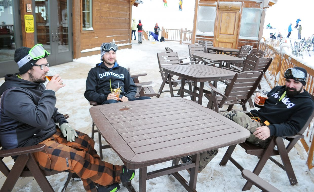 From left, Jamie Knutson, Chris Bishop and Tom LeClair enjoy some drinks on the Four Points Lodge deck during opening day at Steamboat Ski Area on Thanksgiving.