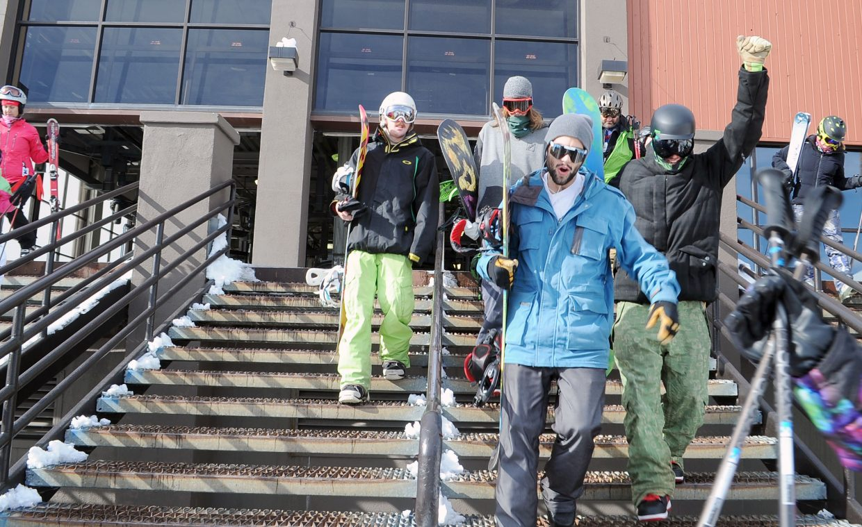 A group of snowboarders heads down the steps of the gondola building Thursday during Opening Day at Steamboat Ski Area.