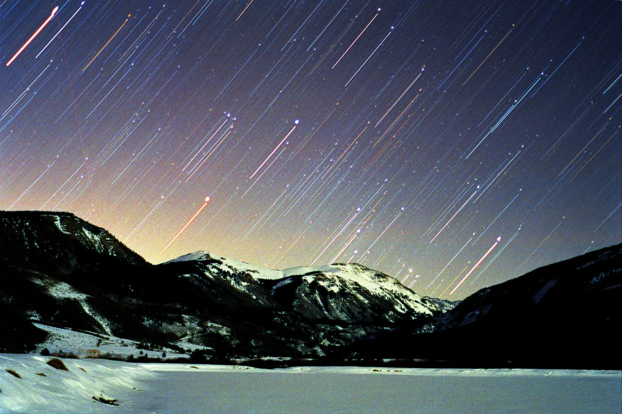 "Orion, the Hunter, was caught ""throwing a leg up over our fence of mountains"" east of Camp Hale, just north of Leadville on Dec. 8, 2002. You can catch Orion in the act around 8 p.m. in the eastern sky during early December."