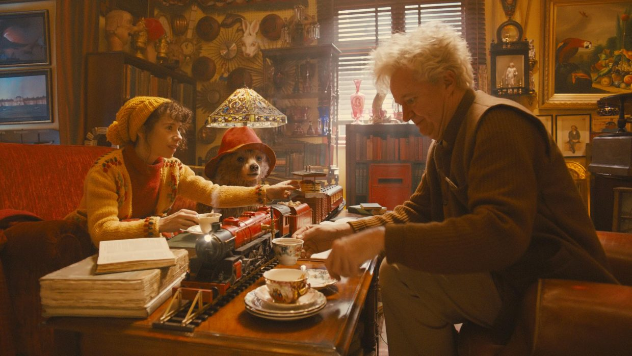 """Mrs. Brown (Sally Hawkins) and Paddington Bear (voice of Ben Whishaw) visit with Mr. Gruber (Jim Broadbent) in """"Paddington."""" The movie is an adaptation of the children's book series about a bear who journeys to London from South America and moves in with a British family."""