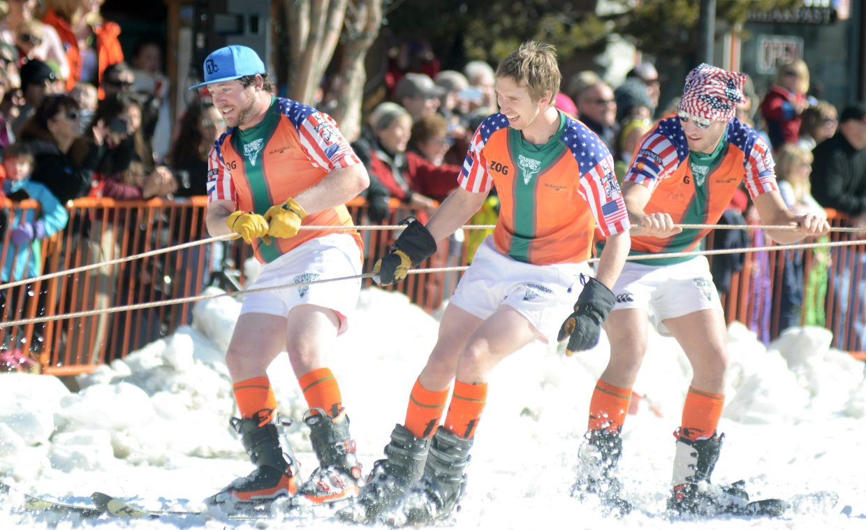 Members of the Steamboat Springs Rugby Club try to stay upright during their tow down Lincoln Avenue as one of the entries in the Winter Carnival's Diamond Hitch Parade.
