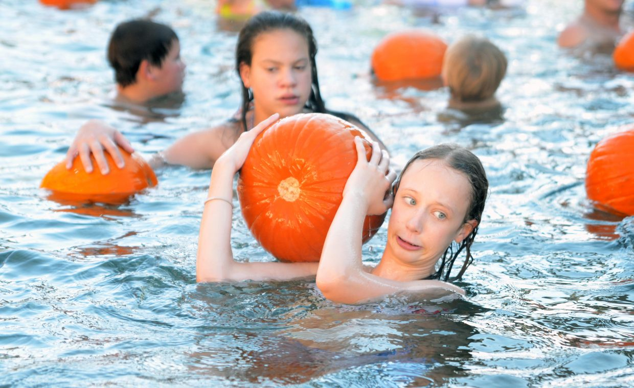 Steamboat Springs Middle School student Lydia Noble, 12, hauls a large pumpkin from the Old Town Hot Springs waters Sunday as part of the 2014 Pumpkin Float.