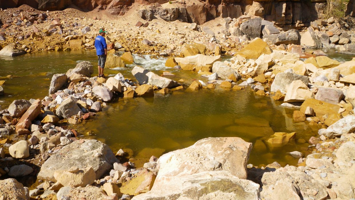 """On Sept. 17, 2012, Dustin Surprenant inspects rockfall at Warm Springs Rapid — a rockfall that set the scene for """"Warm Springs."""" A film produced by Rig to Flip about the rapid will premiere at 7:30 p.m. Friday at Schmiggity's."""