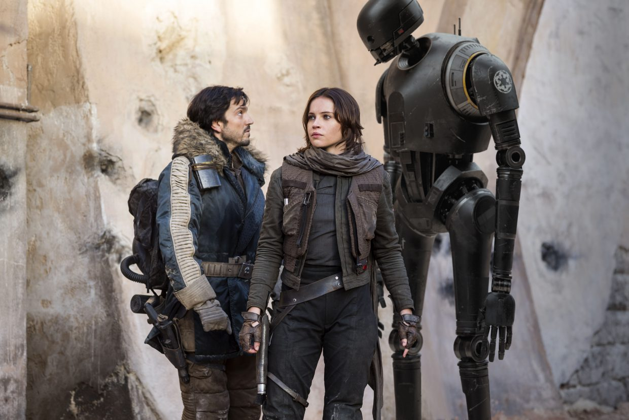 """Cassian Andor (Diego Luna) exchanges words with droid K-2SO (Alan Tudyk) as Jyn Erso keeps watch in """"Rogue One: A Star Wars Story."""" The movie takes place leading up to """"A New Hope"""" as the Rebel Alliance seeks out the plans for the Death Star."""