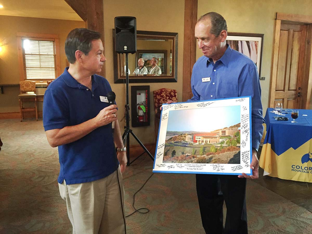Incoming Colorado Mountain College Foundation Regional Development Officer Randy Rudasics, left, presents a signed image of CMC's Alpine Campus to retiring Regional Development Officer Jim Swiggart at his recent retirement party. Observing, and reflected in the mirror, are CMC Foundation Board Chair Bere Neas, left, and local CMC Trustee Ken Brenner. Rudasics will also continue in his role as the manager of the Yampa Valley Entrepreneurship Center, housed at CMC.