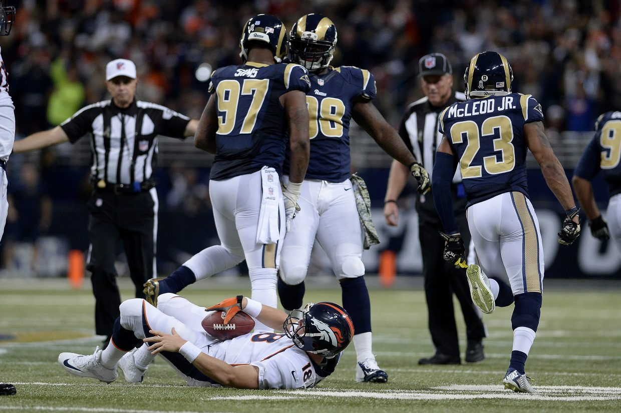 Eugene Sims (97), of the St. Louis Rams, and Kendall Langford (98) celebrate a sack by Aaron Donald (99) on Peyton Manning (18), of the Denver Broncos, during the second half of the Rams' 22-7 win at the Edward Jones Dome. The Denver Broncos visited the St. Louis Rams in a Week 11 NFL showdown.