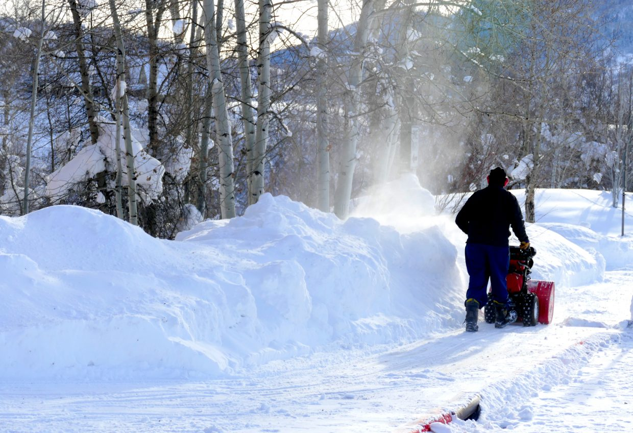 """""""From the Steamboat Springs High School parking lot. Snow removal crews are busy pushing the snow away today, getting ready for the kids to get back to school Monday. A man snowblowing the front sidewalk of the school. Have I mentioned that we have a LOT of snow up here?"""" Submitted by Shannon Lukens."""