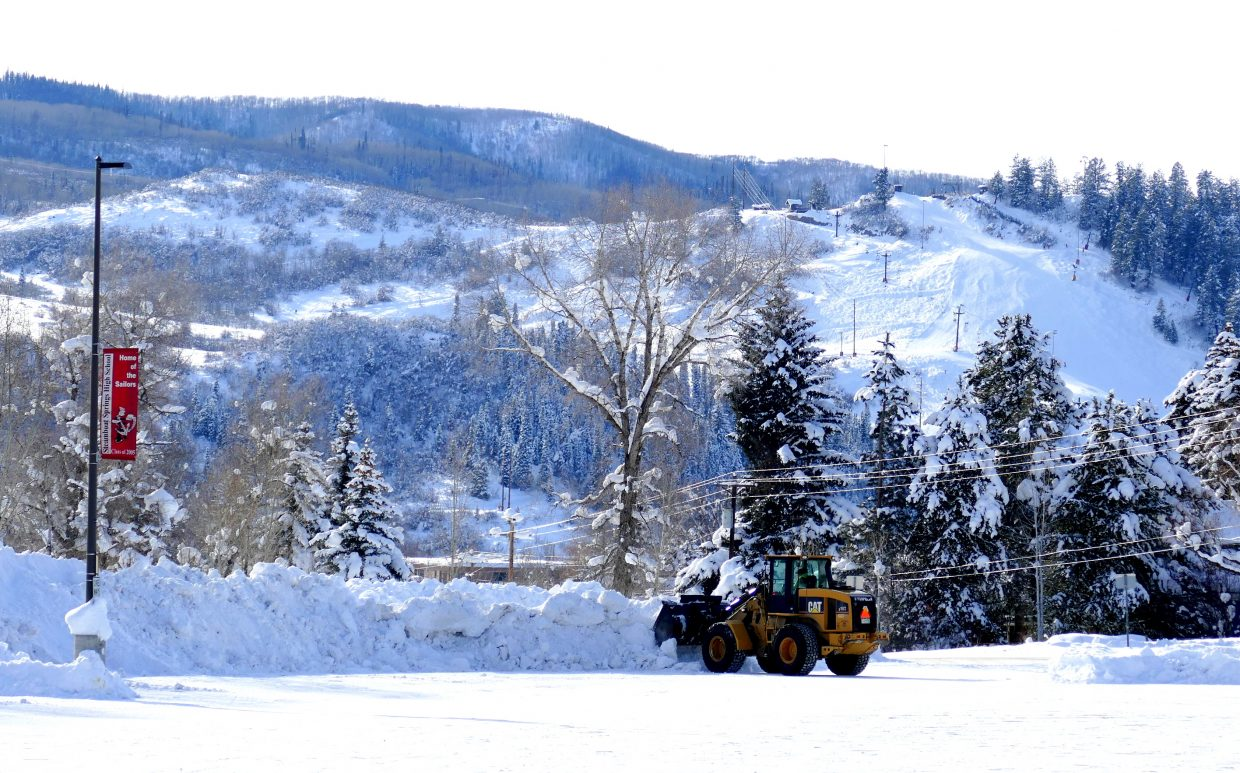 """""""Snow removal crews are busy pushing the snow away today, getting ready for the kids to get back to school Monday. You can see the red banner that says, """"Home of the Sailors,"""" on the left. Yes, the SSHS Sailors. The ski slopes of Howelsen Hill are in the background. You can see the steep piles of snow around the parking lot."""" Submitted by Shannon Lukens."""