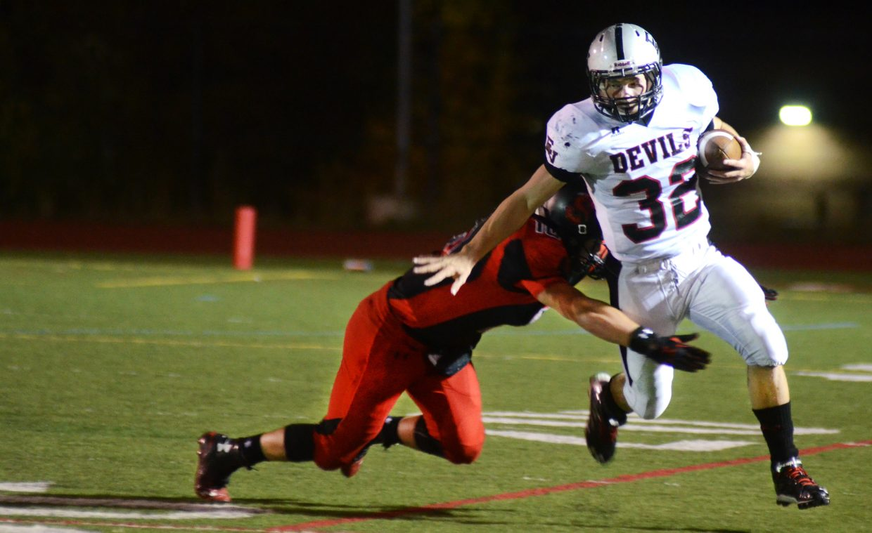 Eagle Valley running back Riley Rowles runs through a Zach Holm tackle in the second half of Steamboat Springs' 25-3 loss Friday night. The Devils racked up 357 yards of offense, 236 in the second half alone.