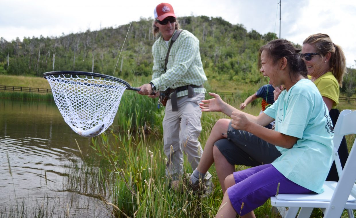 Steamboat Flyfisher guide Todd Krentz holds up STARS client Fiona McClure's catch Friday at the Alpine Mountain Ranch outside of Steamboat Springs. Steamboat Flyfisher teamed up with STARS in the afternoon for lunch and one-on-one lessons.