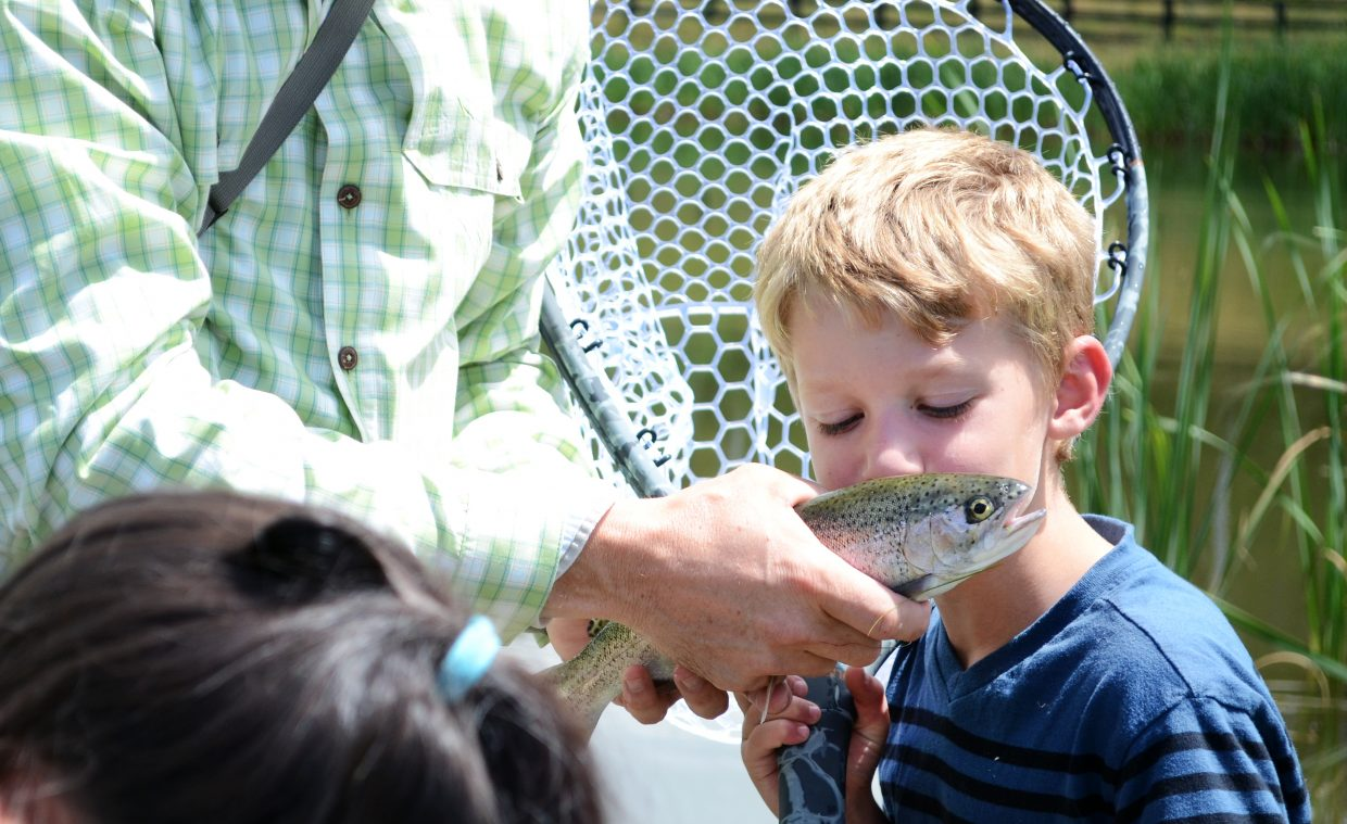 STARS client Cody Pierce gives his rainbow trout a kiss Friday afternoon at Alpine Mountain Ranch. Pierce was with fellow STARS clients who teamed up with Steamboat Flyfisher guides for lunch and one-on-one lessons.