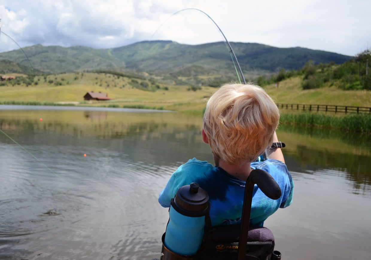 STARS client Casey Myers reels in a fish Friday at Alpine Mountain Ranch. Guided by Steamboat Flyfisher owner Johnny Spillane, Myers caught his first fish of the day.