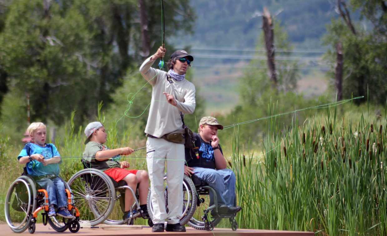 Steamboat Flyfisher owner Johnny Spillane shows STARS clients Casey Myers, Kyle Taulman and Paul Stoiber how its done Friday at Alpine Mountain Ranch. Spillane and fellow guide Todd Krentz shared lunch with STARS clients then gave them a few hours' worth of lessons on the water.