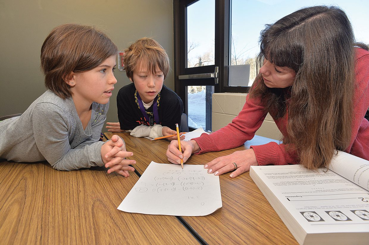 Parent and volunteer math coach Sally Lambert works with Soda Creek Elementary students Indiana Kretzschmar, right, and Suzy Magill in January. Lambert was named the Steamboat Springs School District's Friend of Education for the 2014-15 year during a school board meeting Monday night.