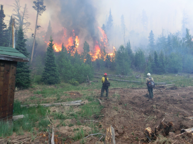 Firefighters keep an eye on the Beaver Creek Fire near a structure. The fire is expected to grow.