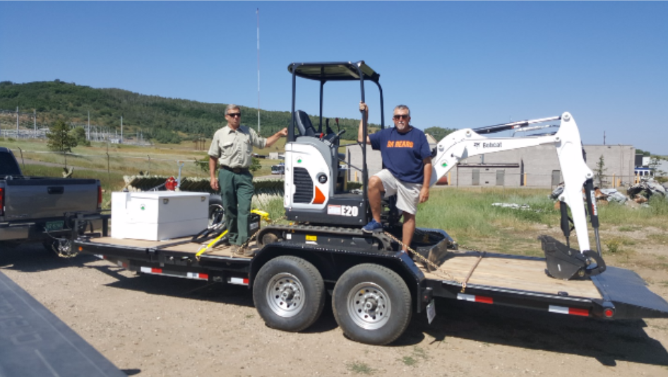 Kent Foster, left, and Rene Waters pose with the new mini-excavator that will help to maintain motorized trails in Northwest Colorado.