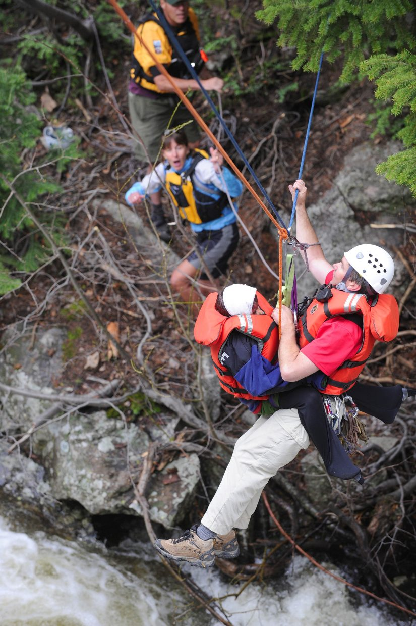 Routt County Search and Rescue President Russ Sanford takes Kade Green across Fish Creek. This photograph was taken by Matt Stensland and appeared in the June 14, 2009, edition of the Steamboat Today.
