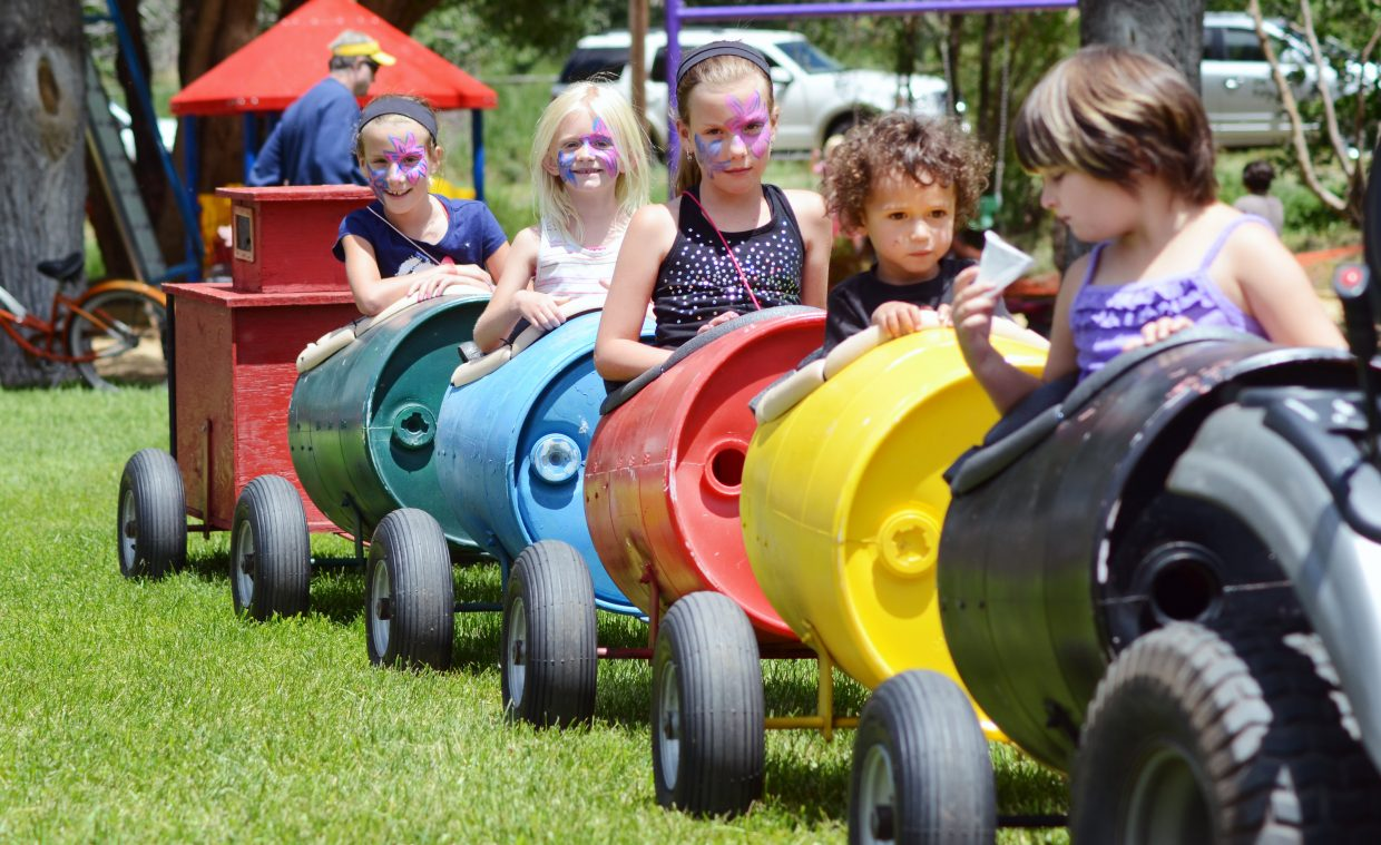 A group of kids do the tractor train ride Saturday afternoon at Taste of South Routt in Oak Creek's Decker Park.