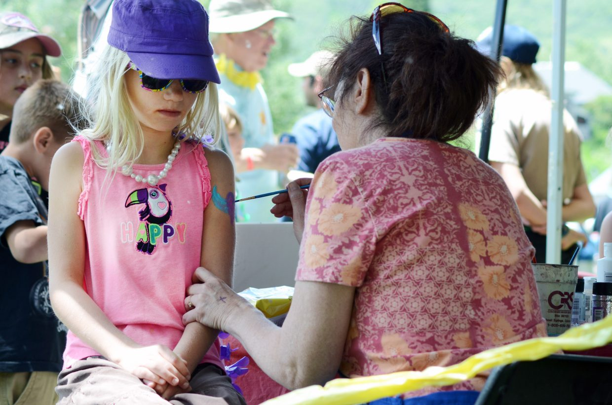 Autumn Oslowski, 9, gets a heart painted on her arm at Miss Suzy's Face Painting booth at Taste of South Routt in Oak Creek on Saturday afternoon.