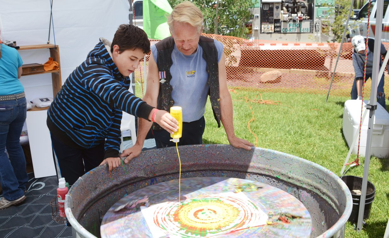 Johnny Barkal, 12, squirts a little yellow paint into his spin art creation with help from Charlie Holthausen on Saturday afternoon at Taste of South Routt in Oak Creek.