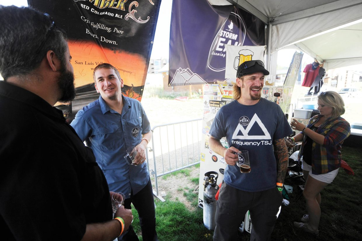 Storm Peak Brewing Co. brewers Wyatt Patterson, center left, and brother Tyler Patterson, center right, visit with Butcherknife Brewing Co. brewer Mark Fitzgerald during OktoberWest in September.