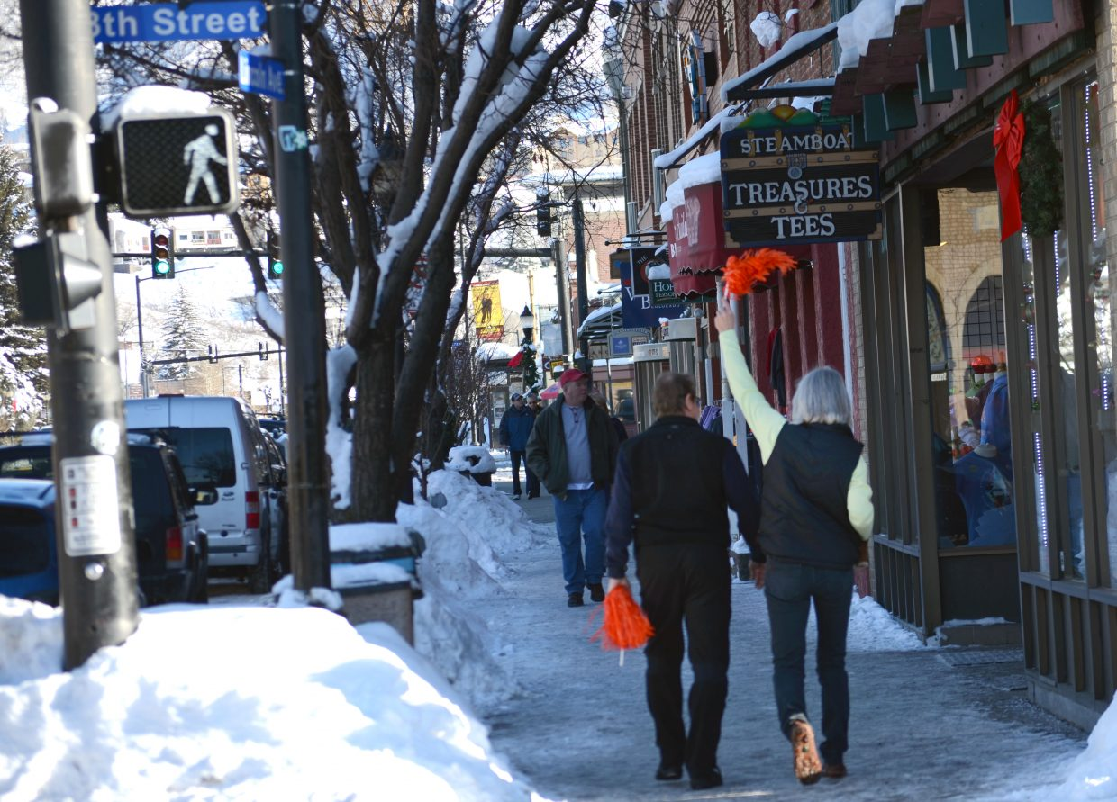 A woman walks down Lincoln Avenue in downtown Steamboat Springs waving an orange pom pom before the start of Super Bowl XLVIII.