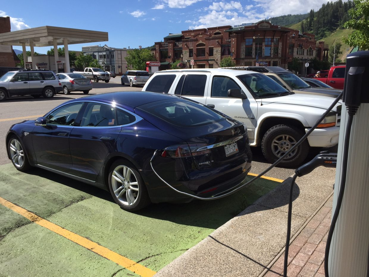 A Tesla charges up at the city's free charging station on 10th Street.