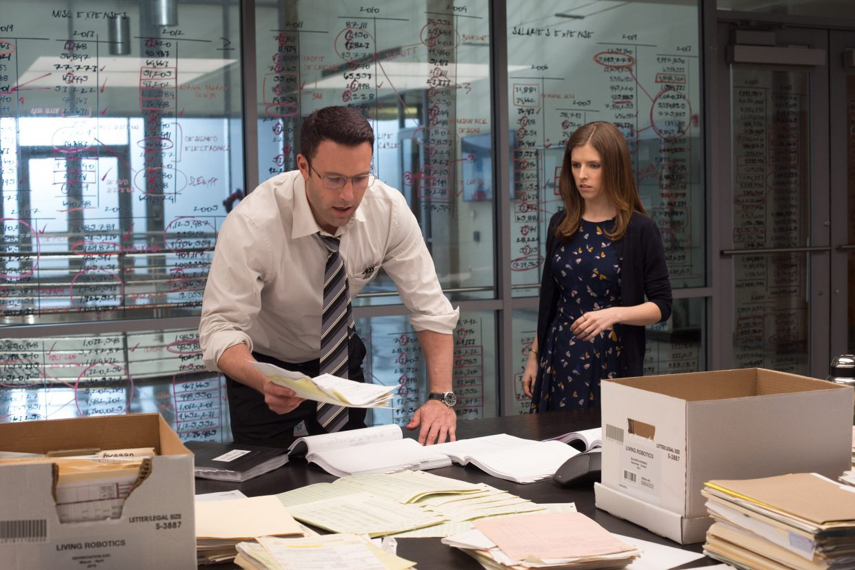 "Christian Wolff and Dana Cummings (Ben Affleck, Anna Kendrick) look over documents in ""The Accountant."" The movie is about a mathematical genius who leads a dangerous double life."
