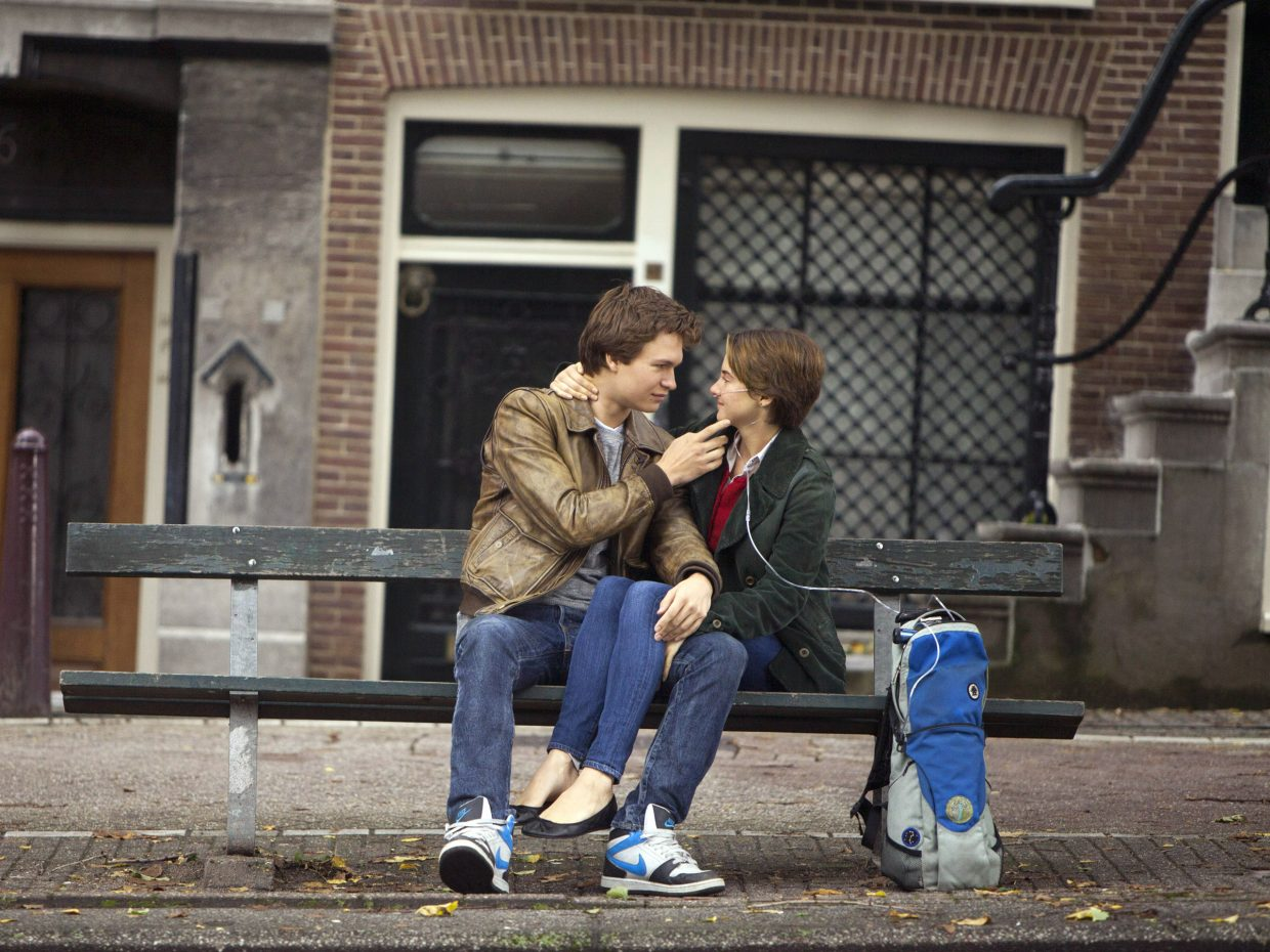 "Augustus Waters and Hazel Grace Lancaster (Ansel Elgort, Shailene Woodley) share a longing look in ""The Fault in Our Stars."" The movie is about a terminally ill teenage girl who falls in love with a boy also affected by cancer despite her better judgment."