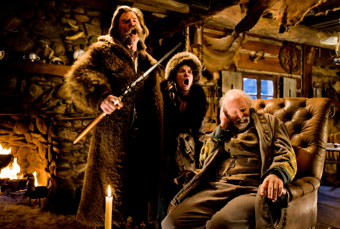 """John Ruth and Daisy Domergue (Kurt Russell, Jennifer Jason Leigh) bellow over the roaring wind, much to the annoyance of their fellow guest (Bruce Dern) in """"The Hateful Eight."""" The movie is a Western about a number of strangers who are stuck in a lodge during a blizzard."""