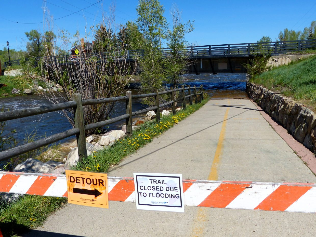 Trail closed sign next to the C-Hole, which goes under the bridge at the library. The water is high here so the trail is closed right now while the snow melts off the mountain. Submitted by: Shannon Lukens