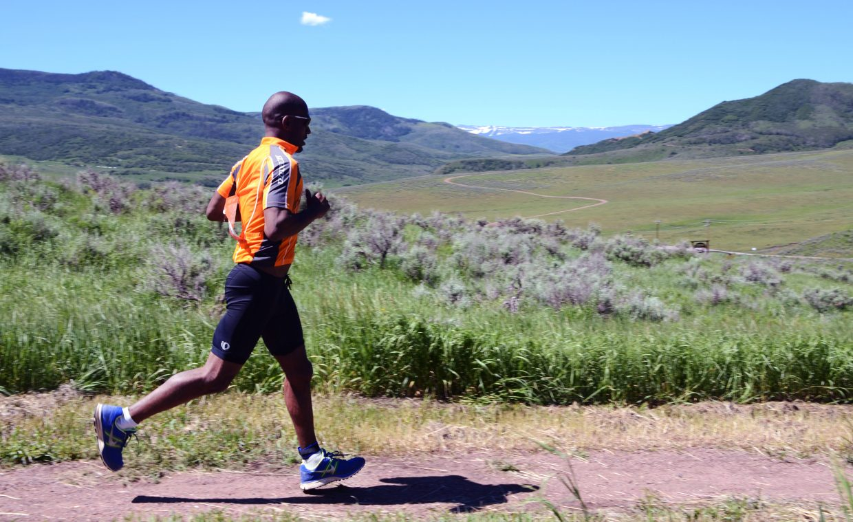 David Veney II gets some sprawling views of the Flat Tops Wilderness Area during the final stretch of the Tri the Boat triathlon at Stagecoach State Park on Sunday.