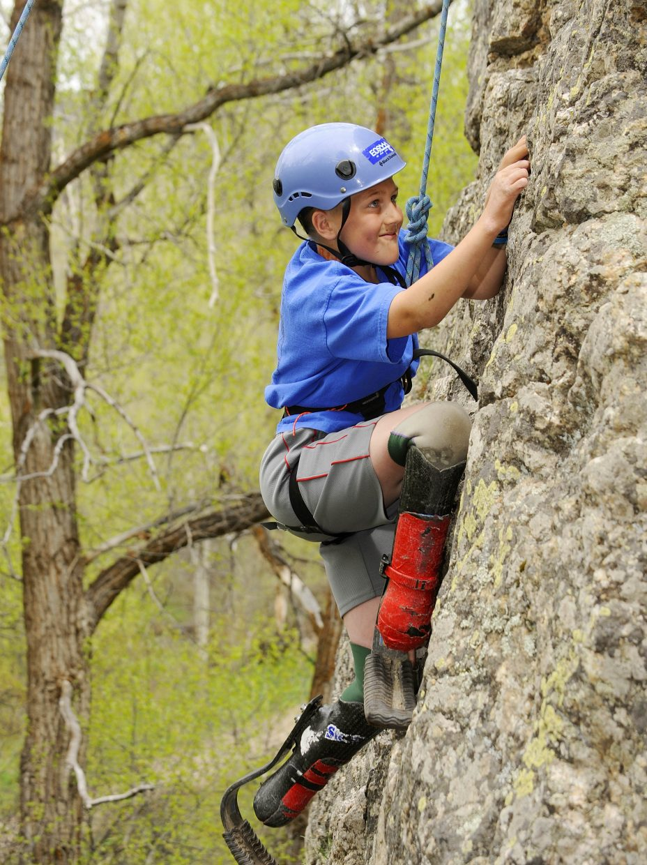 Tyler Johnson climbs a rock face in Butcherknife Canyon as a sixth-grader in 2010. It was Johnson's first time climbing the rock with his prosthetic legs, he said. This weekend, he will head to a special youth amputee camp in Ohio for the fifth time. He will be a junior in the fall.