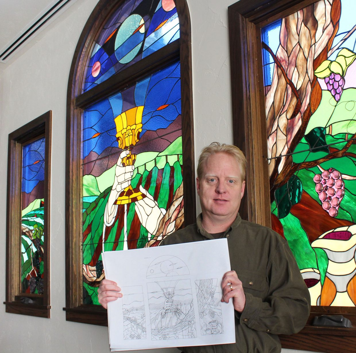 Artist Gregory Effinger shows an original art drawing that would eventually become the spectacular stained glass window behind him at the Holy Name Catholic Church in Steamboat Springs.
