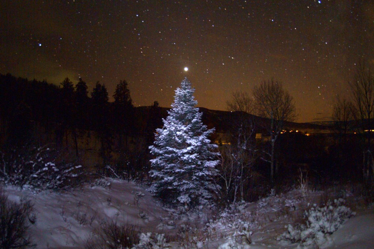 The dazzling Evening Star, Venus, adorns the top of this snowy evergreen tree with the lights of Stagecoach in the background in an image taken Dec. 14, 2008. Now, eight years later, Venus has gone full cycle and is back as the Evening Star in the December sky. Watch for it after sunset each evening throughout the coming winter.