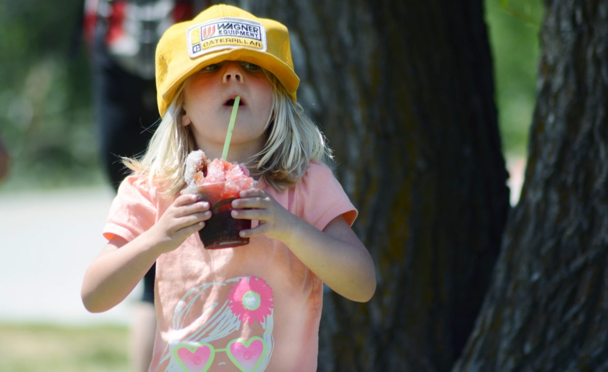 Van Chapman, 3 1/2, escapes the sun with a hat, snow cone and some shade Sunday during the final day of Art in the Park at West Lincoln Park.
