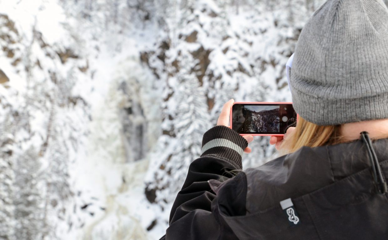 Ciara Summers, 22, lines up a photo of Fish Creek Falls with her cellphone Sunday afternoon. After a cold, snowy start to the weekend, Sunday saw no snow but temperatures also didn't reach the 20s. More clear weather is expected to last through the week.