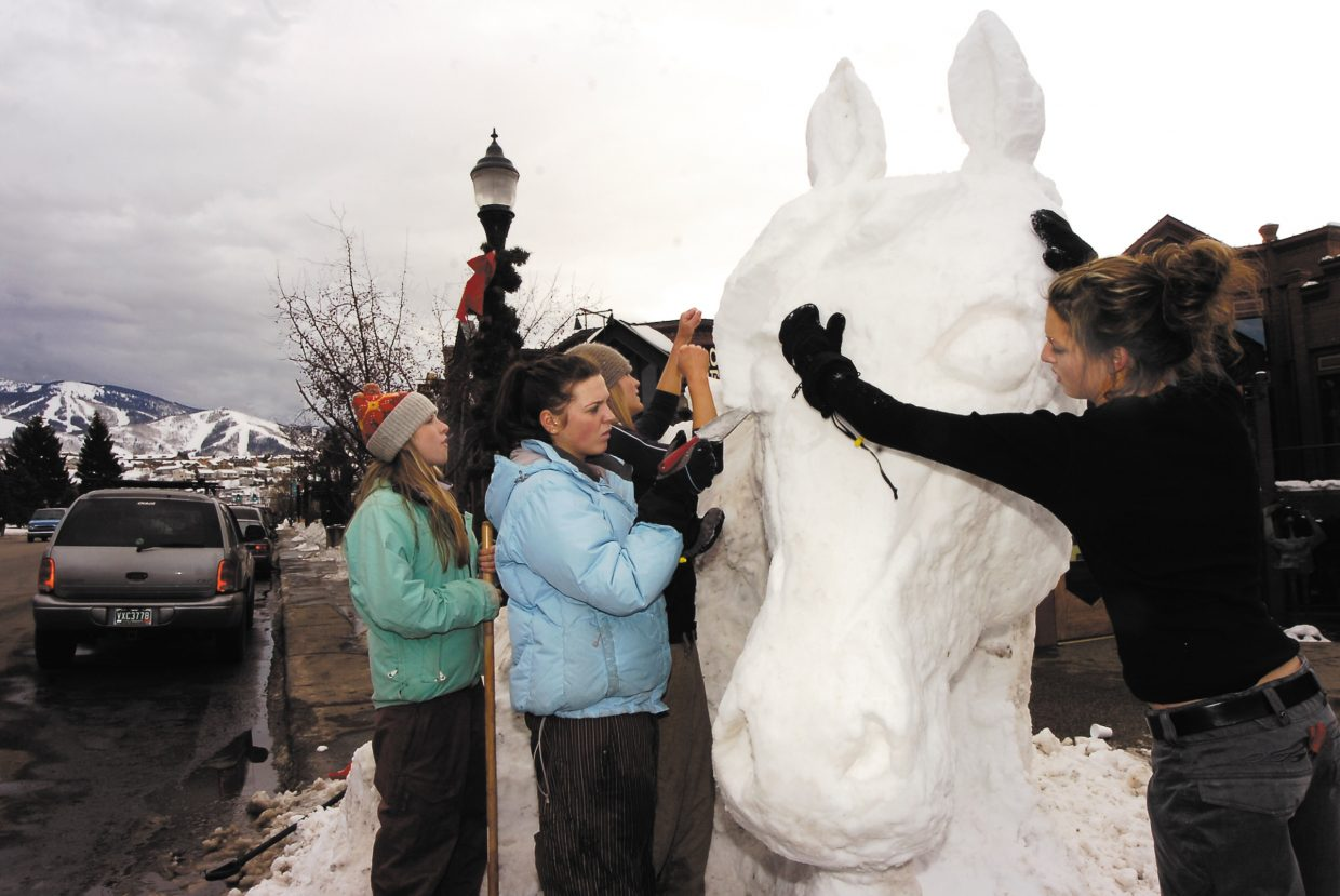 Katy Gary, from right, Tara Conlin and Miranda Schrock finish a few last-minute details to their snow sculpture during Winter Carnival in 2007.