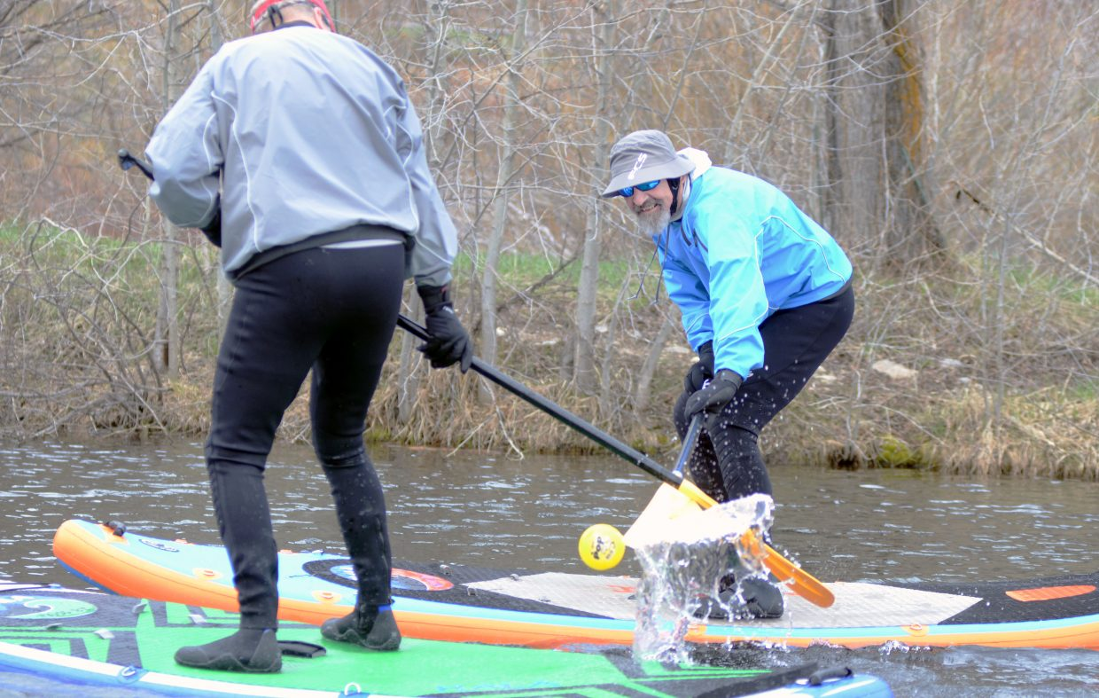 Robert, right, and Tom (they preferred to not give their last names) play their version of stand-up paddleboard polo Sunday afternoon at Fetcher Pond. There were plenty of trail- and park-goers out and about in between storms.